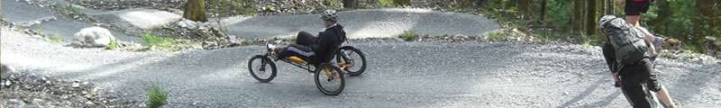 Riding an adaptive mountain bike in the woods at Coed y Brenin in Snowdonia